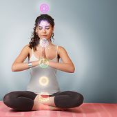 image of mantra  - Beautiful young woman doing yoga meditation in lotus position with activated chakras over body - JPG