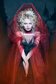Glamorous Blonde Girl In A Maroon Cape With Stunned Hairdo. Fairy Tale Character