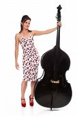 stock photo of double-bass  - An attractive Rockabilly girl wearing a cherry print dress smiling and posing with a double bass - JPG