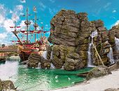 stock photo of sailing vessel  - Pirate ship in the backwater of tropical pirate island with big rock in form of skull near it - JPG