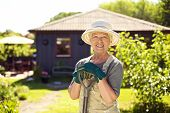 Cheerful Elder Woman With Gardening Tool In Backyard