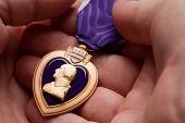 Homem segurando a medalha de guerra Purple Heart