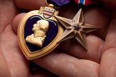 Homem segurando coração roxo e medalhas de Bronze de guerra