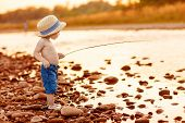 stock photo of overalls  - Adorable baby on river with fishing - JPG