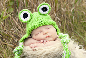foto of baby frog  - Newborn baby sleeping in a country setting with a frog crochet hat on - JPG