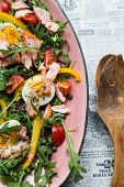 Salad With Salmon And Verdure In Pink Plate On Retro Newspaper Background