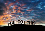 "Inspirational silhouetted words ""You got this"" on a hillside with colorful sunset clouds."