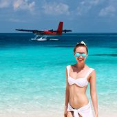Woman in bikini at tropical beach. Seaplane at background.