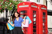 England London shopping woman shopper holding shopping bags by red phone booth. Female shopper smili