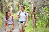 Hikers - hiking people walking happy in forest. Hiker couple laughing and smiling. Interracial coupl