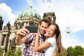 Travel couple selife self portrait, Berlin, Germany. Happy tourists people in front of Berlin Cathed