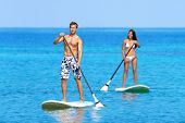 Paddleboard beach people on stand up paddle board surfboard surfing in ocean sea on Big Island, Hawa