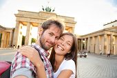 Happy couple selfie selfportrait in front of Brandenburg Gate or Brandenburger Tor, Berlin, Germany.