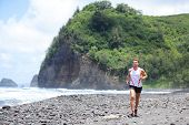 Trail running athlete man training for fitness and marathon living healthy lifestyle outside in beautiful landscape on Big Island, Hawaii, USA. Fit male sports runner model.