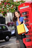 London woman talking happy on smartphone shopping holding shopping bags by red phone booth. Female s