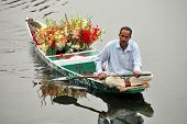 SRINAGAR, JAMMU AND KASHMIR, INDIA - JULY 20, 2006: Flower seller on Dal Lake in Srinagar rowing his