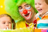 Kids With Clown Celebrating Birthday Party And Blowing Candles On Cake