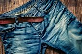 Detail Of Blue Jeans With Leather Belt In Vintage Style
