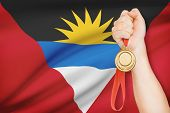 Medal In Hand With Flag On Background - Antigua And Barbuda