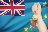 Medal In Hand With Flag On Background - Tuvalu