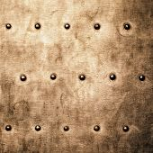 foto of stelles  - Closeup of grunge gold brown metal plate with rivets and screws as background or texture - JPG