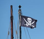 stock photo of pirate sword  - A Pirate Flag Flying at the Top of a Ships Mast - JPG