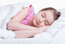 stock photo of nighties  - Adorable little girl in pink nightie sleeps in the bed on a white background - JPG