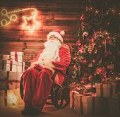 Santa Claus sitting on rocking chair in wooden home interior with illuminated decoration on a wall