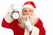 Santa Claus with alarm clock showing five minutes to midnight making shhh gesture and looking at cam