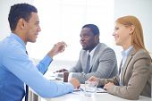Group of confident business partners interacting at meeting in office
