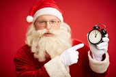 Happy Santa pointing at clock showing five minutes to midnight on red background