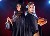 Two witches with lantern and pumpkin looking at camera in the dark