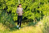 Young Woman Jogging In Summer Morning Park