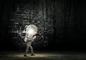Tired businessman carrying light bulb on his back