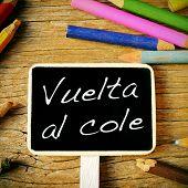 the sentence vuelta al cole, back to school written in spanish in a blackboard label, on a wooden de
