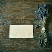 a bunch of lavender flowers and a blank signboard on a rustic wooden table