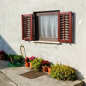 Old Traditional Window With Open Wooden Shutters And Flowers In Croatia