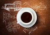Close up of cup of coffee and construction sketches at background
