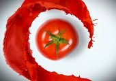 Fresh red tomato and splashes at background