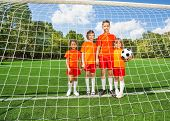 Children of different height stand with football