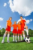 Happy kids of different height with football