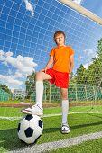 Boy in uniform with leg on football near woodwork