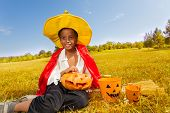 Halloween boy sits on yellow grass with pumpkin