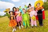 Children in different Halloween costumes standing