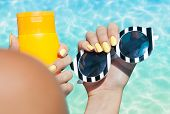 Summer fashion and beauty hand care concept, woman holding sunglasses and sunscreen lotion at the po