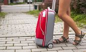 Travel concept, the girl's legs and red suitcase outdoors.