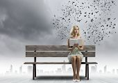 Young pretty woman sitting on bench and reading book