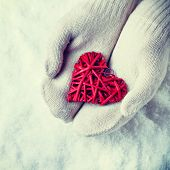 Woman hands in white knitted mittens are holding a beautiful red heart in a snow background. Love an
