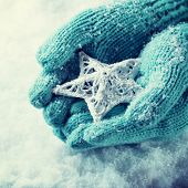 Woman hands in light teal knitted mittens are holding a beautiful white star in a snow background. Love and St. Valentine concept. Instagram effect.