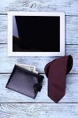 Tablet, wallet and tie on wooden background